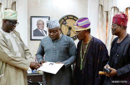 Hon. Obasa receiving documents from Otunba Deji Osibogun while Dr. Amos Akingba and Chief Tola Adeniyi look on.